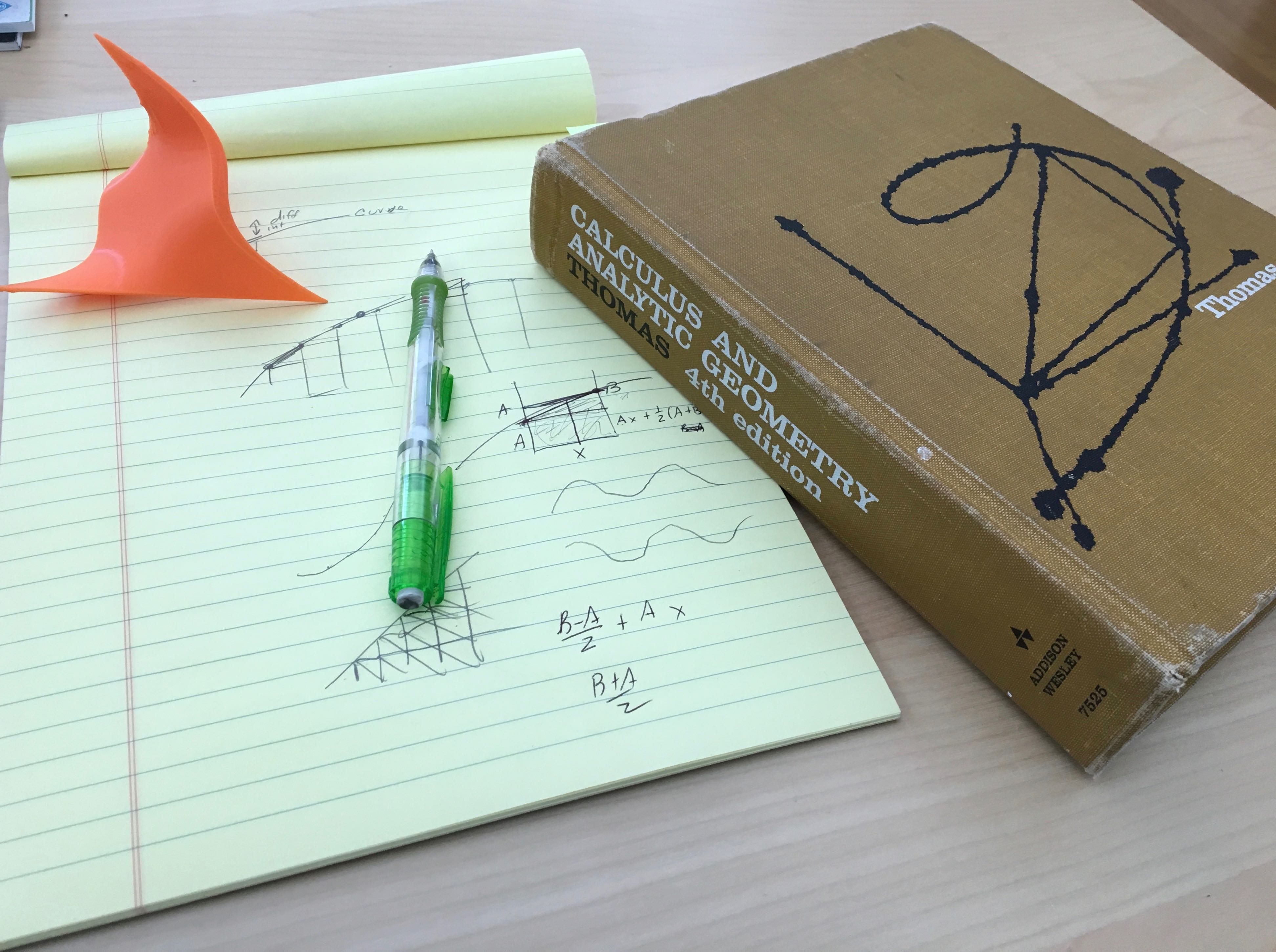 Old, battred Calculus 1 text, a pad with scribbles, and a 3D print of a math function